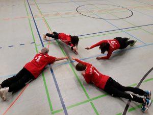 Die vier Spielerinnen der SG HoKaMü bei den Vorbereitungen für das Turnier. Alle vier Spielerinnen liegen auf dem Boden mit dem Kopf in der Mitte und den Füßen nach außen. Dehn- und Aufwärmübungen des zukünftigen Deutschen Meisters 2018